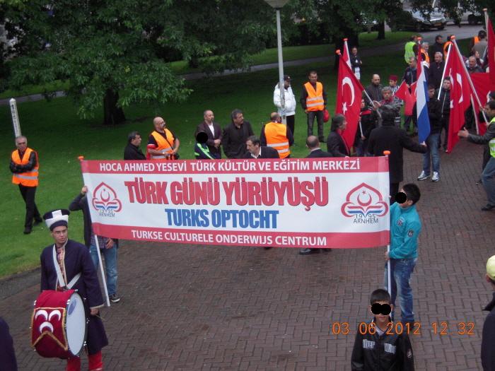 Spandoek tijdens de optocht van 2012 waaruit duidelijk wordt dat de organisatie in handen is van de vereniging Hoca Ahmed Yesevi. Op de trommel zien we de MHP-vlag met de drie halve manen.