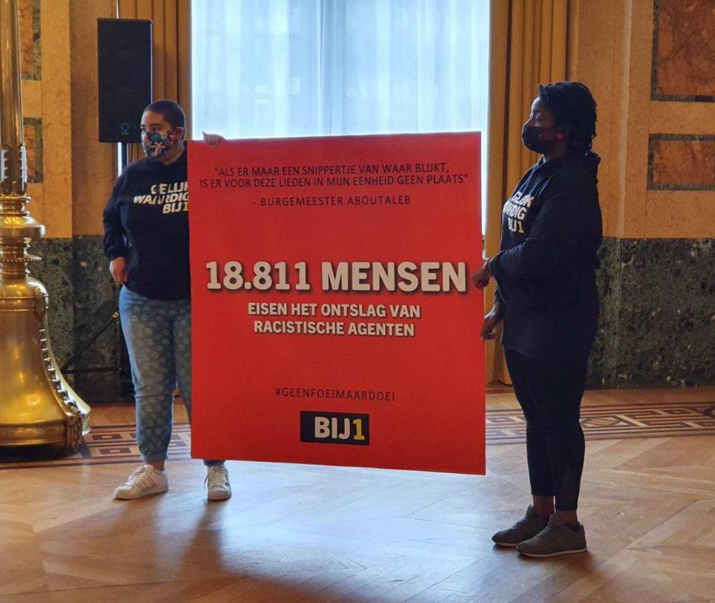 Twee personen die de enorme rode kaart vasthouden die werd overhandigd aan de burgemeester en de politiebaas