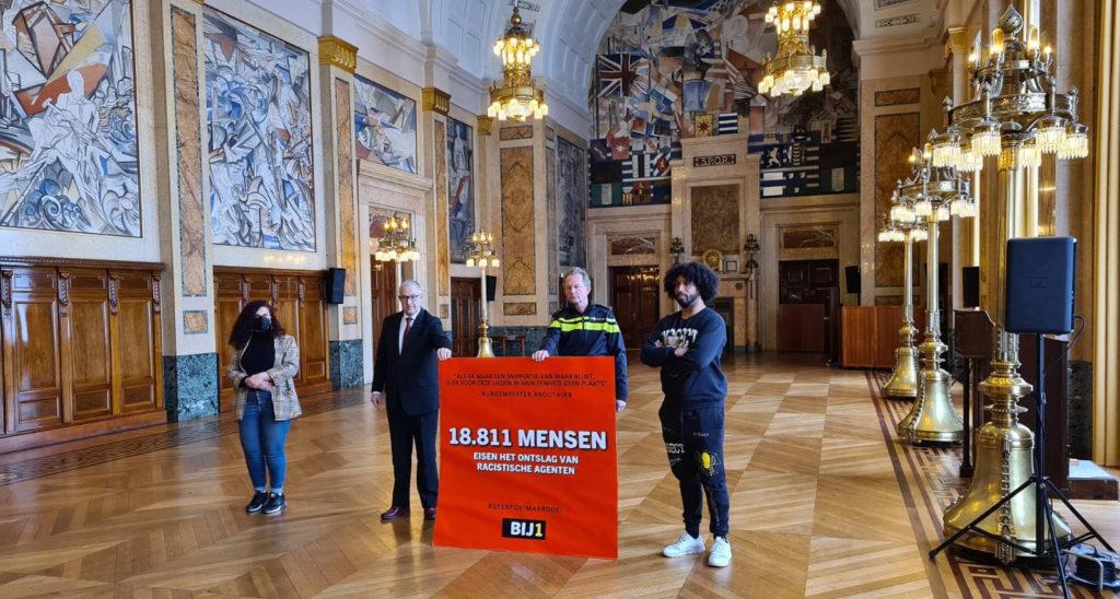 De burgemeester en de politiebaas houden met frisse tegenzin de rode kaart vast voor de foto. Dean Bowen en Sandra Salome staan aan weerszijden.