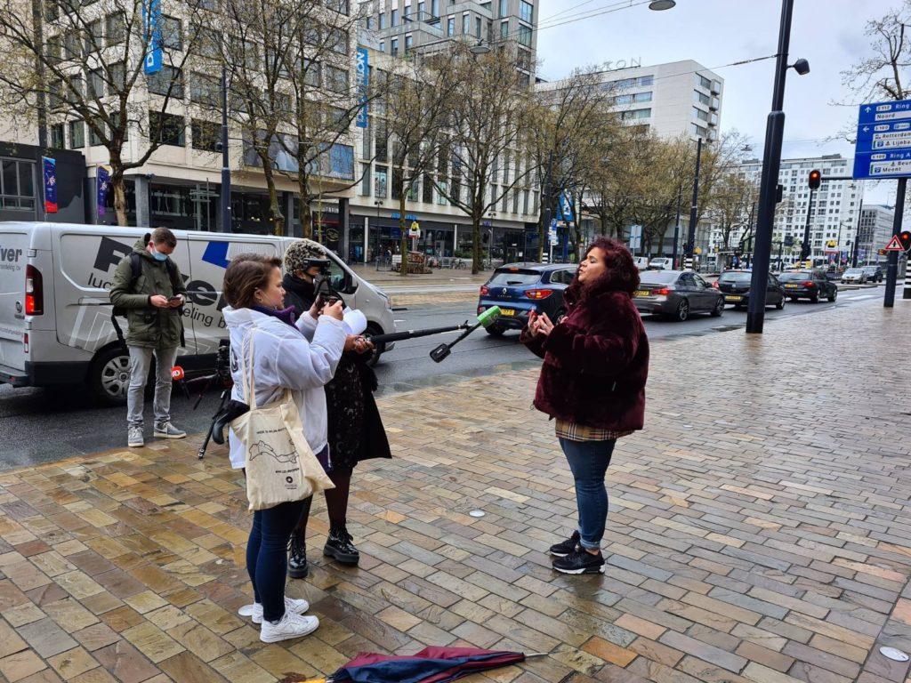 Sandra Salome geeft buiten voor het stadhuis een interview aan de pers. Het is regenachtig weer. Sandra draagt een auberginekleurige fluffy jas van nepbont.