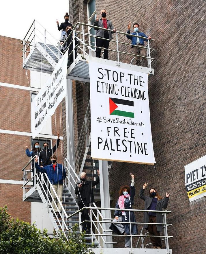 """Brandtrappen met daarop een aantal mensen en een groot spandoek met de tekst """"Stop the ethnic cleansing / #SaveSheikhJarrah / Free Palestine"""". Op de zijkant van de brandtrap zit ook een spandoek maar dat is niet goed leesbaar."""