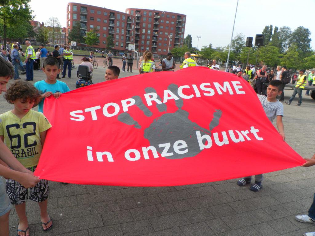 """Kinderen met een groot, rood spandoek met daarop een hele grote grijze handafdruk en de tekst """"STOP RACISME in onze buurt""""."""