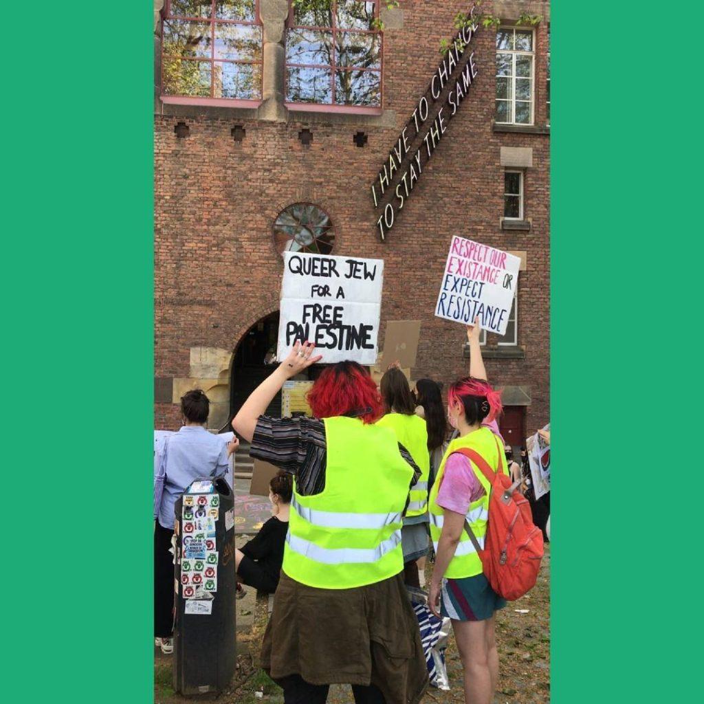 """Demonstranten bij het schoolgebouw. Twee borden zijn zichtbaar, eentje met de tekst """"Queer Jew for a free Palestine"""" en eentje met de tekst """"Respect our existence or expect resistance""""."""