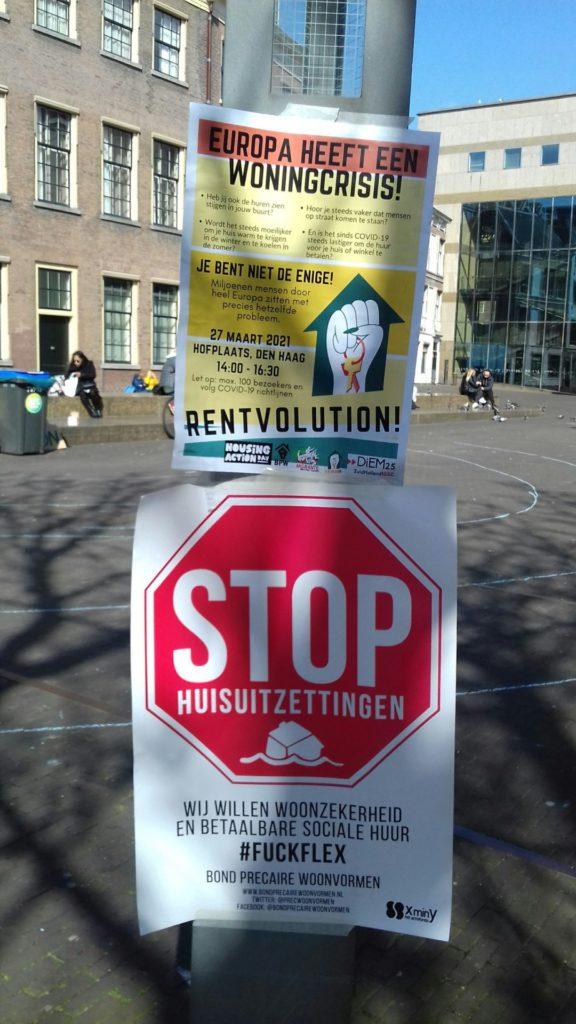 """Twee protestborden die zijn vastgemaakt aan een stuk straatmeubilair.  """"Stop huisuitzettingen, wij willen woonzekerheid en betaalbare sociale huur, #FuckFlex""""  """"Europa heeft een woningcrisis! Je bent niet de enige! Rentvolution!"""""""