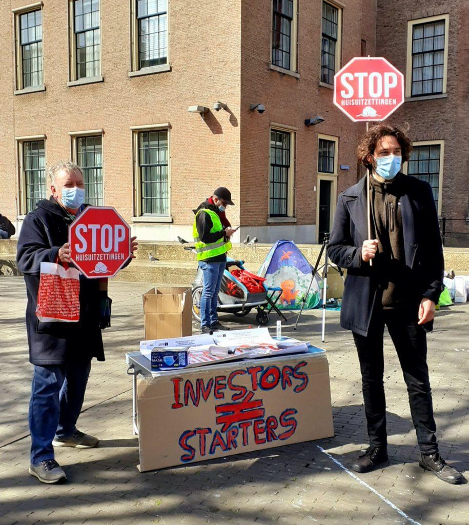 """Twee personen met stop-borden zoals die ook in het verkeer worden gebruikt met onder het woord """"stop"""" het woord """"huisuitzettingen""""."""