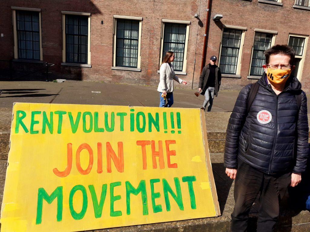 """Eén van de activisten, in een donkerblauwe glanzende jas naast een geel bord met groene en rode tekst """"Rentvolution!!! Join the movement""""."""