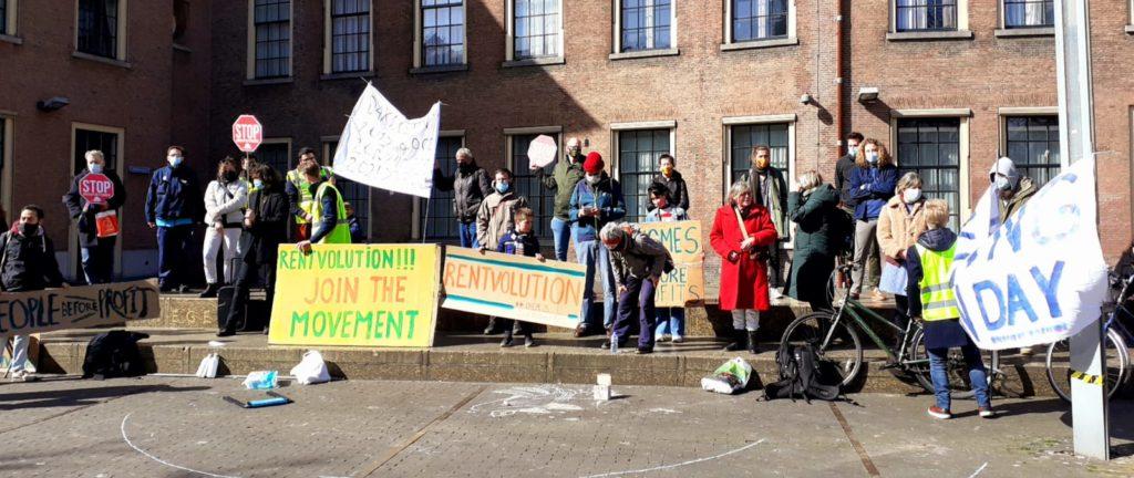 """De groep demonstranten in Den Haag. Diverse protestborden zijn zichtbaar, op het grootste staat """"Rentvolution!!! Join the movement""""."""