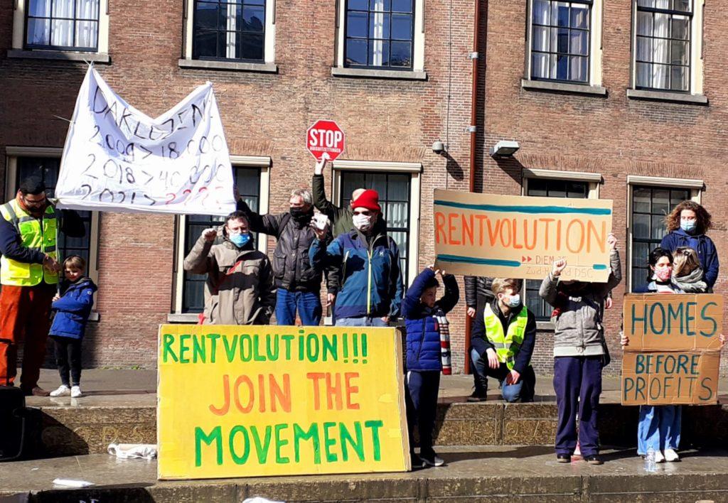 """Diverse demonstranten, onder andere met een bord met de tekst """"Homes before profits""""."""