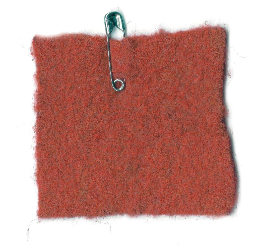 Rood vilten vierkantje aan een veiligheidsspeld, symbool van de actie.