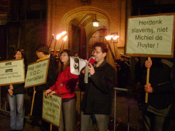 """7 november 2007. Doorbraak-actie bij de ingang van de Nieuwe Kerk op de Dam in Amsterdam tegen een besloten feestje in het kader van het Michiel de Ruyter-jaar. Met actieborden als """"Herdenk slavernij, niet Michiel de Ruyter!"""", """"De Ruyter legde de basis voor de slavernij"""", """"Weg met de V.O.C.-mentaliteit"""" en """"Tegen nationalisme, tegen verheerlijking De Ruyter""""."""
