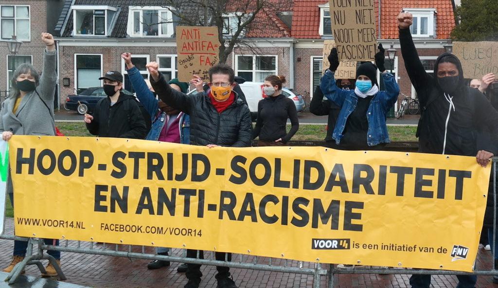 """Demonstranten met een geel spandoek met de tekst """"hoop - strijd - solidariteit en anti-racisme"""" en verwijzigingen naar Voor 14. Op de achtergrond meer demonstranten met verschillende borden, tegen een achtergrond van oude, typisch Nederlandse huisjes."""