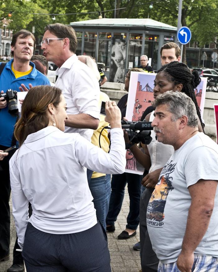 Eerdmans discussieert buiten met tegendemonstranten, terwijl Umar iedereen filmt die iets tegen haar zegt.