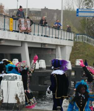 """De bekende """"Zwarte Piet is racisme""""-spandoeken linksboven terwijl Sinterklaas de stad binnenvaart"""