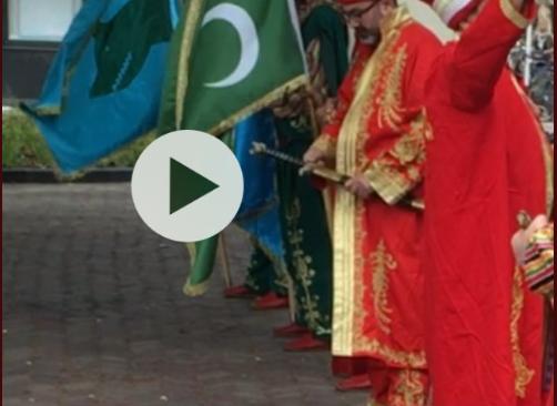 Screenshot van een video van voor het begin van de optocht. In beeld twee Grijze Wolven-vlaggen. De blauwe met de wolvenkop werd in de bus gelegd, de andere met de drie halve manen werd wel meegedragen.