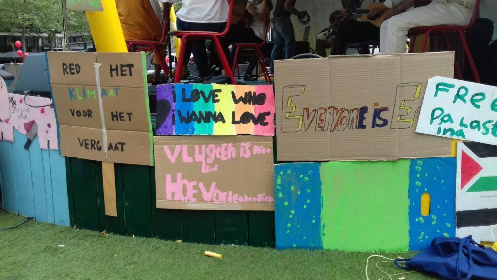 Kleurige protestborden aan de rand van het podium.