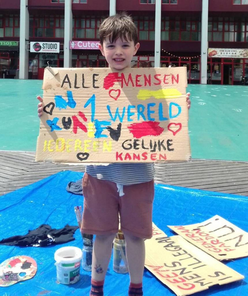 """Een kind met een zelf beschilderd kartonnen bord. Er staat op: """"Alle mensen, 1 wereld, iedereen gelijke kansen"""", eromheen allemaal hartjes."""