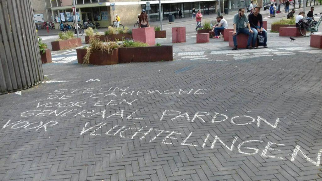 """Leus op de grond """"Steun de campagne voor een generaal pardon voor vluchtelingen""""."""