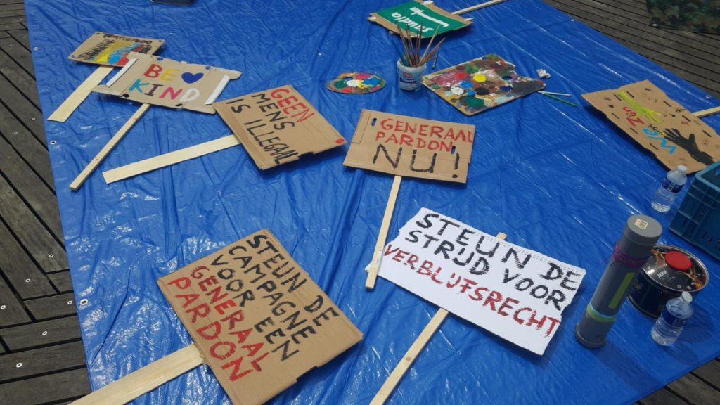 Een voorraadje protestborden op het dekzeil.