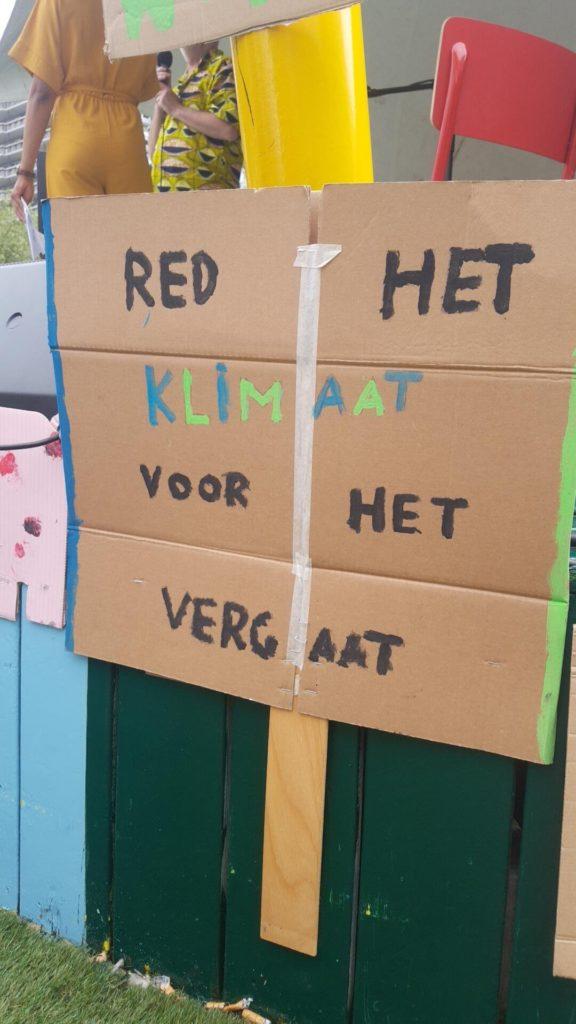 """Een bord met de tekst """"Red het klimaat voor het vergaat""""."""
