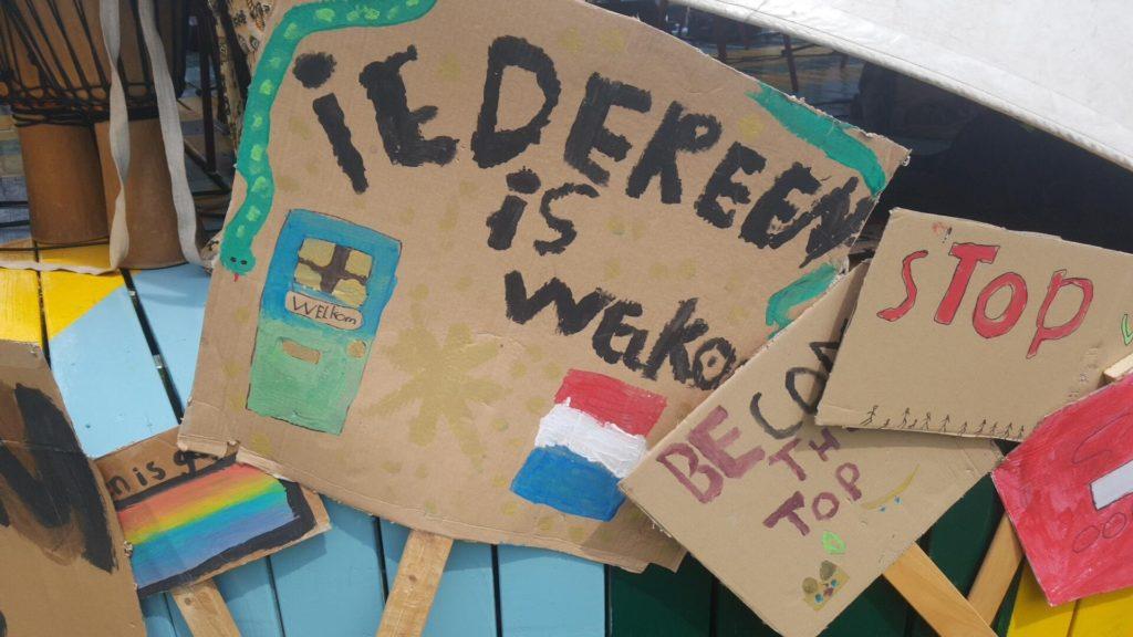 """Een bord met daarop een deur en een slang en een Nederlandse vlag met de tekst """"Iedereen is welkom""""."""