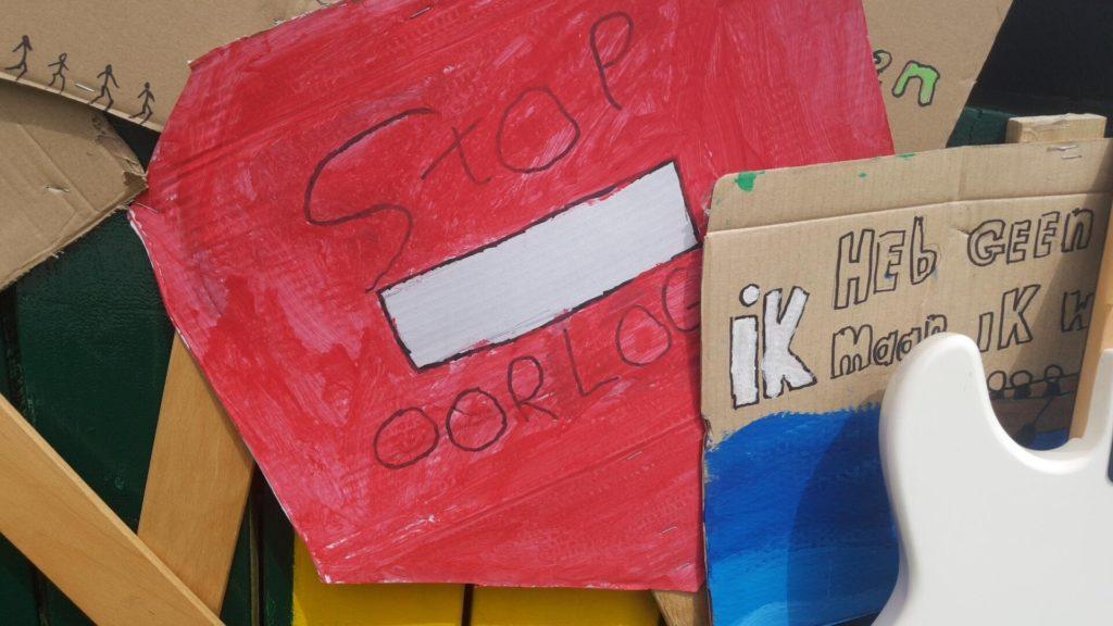 """Een stopbord (verkeersbord) met de tekst """"Stop oorlog""""."""
