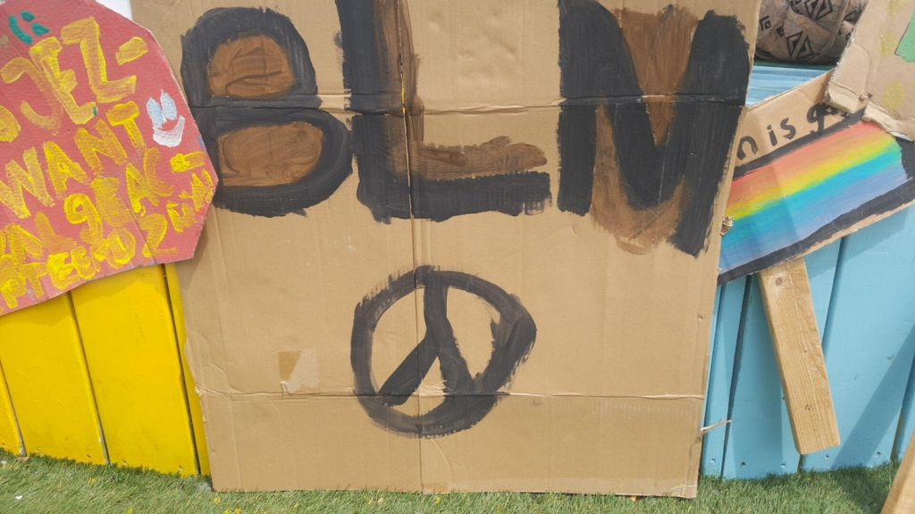 """Een bord met de letters """"BLM"""" en een vredesteken."""