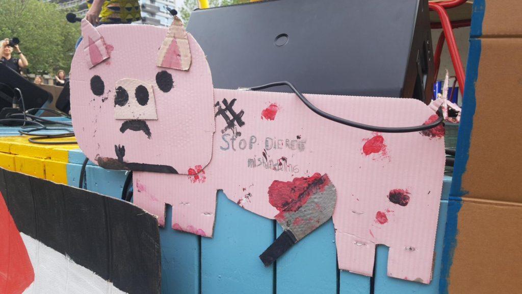 """Een bord in de vorm van een varkentje met de tekst """"Stop dierenmishandeling""""."""