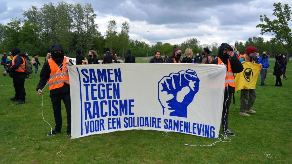 """Twee activisten met het spandoek """"Samen tegen racisme - voor een solidaire samenleving""""."""