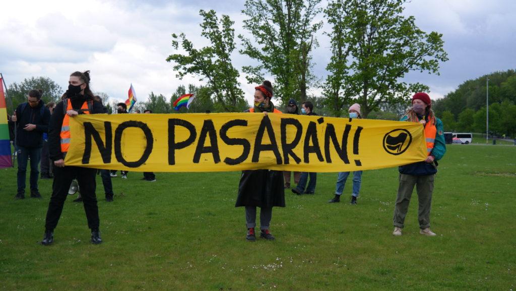 """Drie activisten met het """"No pasarán!""""-spandoek."""