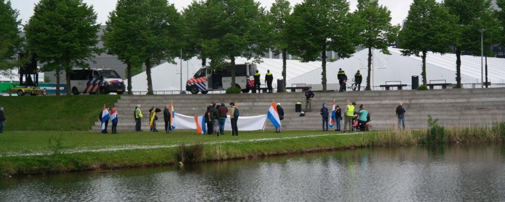 De 15 nazi's met hun NSB-/Prinsenvlaggen. Ze staan flink voor lul met hun sneue groepje.