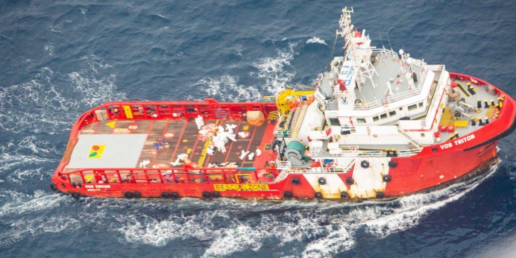 Foto van het rood met witte schip Vos Triton. Je ziet mensen in witte pakken op het dek.  Het gaat om een schip dat normaal gesproken boorplatformen verankert aan de zeebodem.