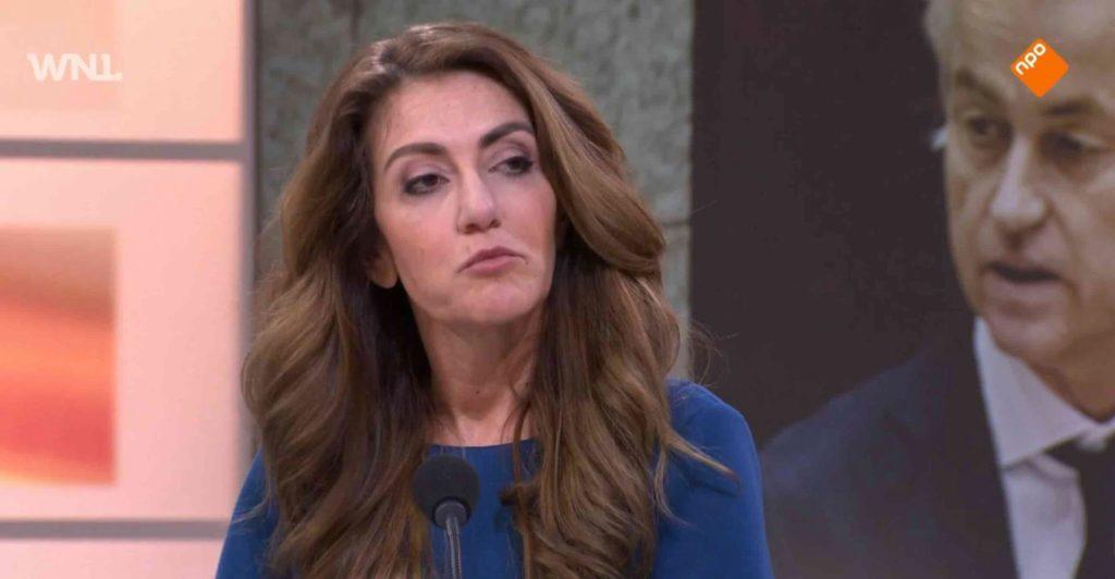 Dilan Yeşilgöz bij WNL op TV. Op het scherm achter haar zie je Geert Wilders.