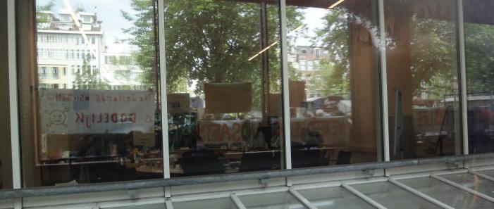 Weerspiegeling van de actie op de binnenramen van het stadhuis.