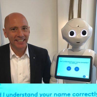 """Ton Wilthagen naast een vriendelijk uitziende mensachtige robot met een tablet waar op staat """"Did I understand your name correctly?""""."""