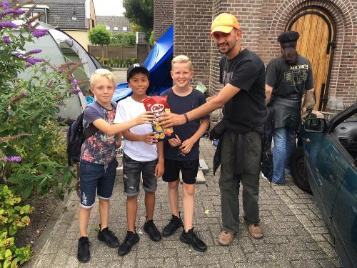 Drie jongetjes komen een zak chips brengen voor de vluchtelingen in Wormer.