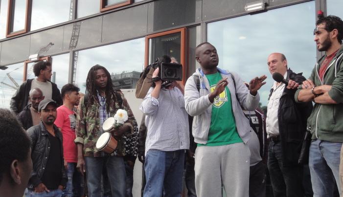 """Woordvoerder Yusuf bij het startpunt van de demonstratie, het kraakpand """"Vluchtgemeente""""."""