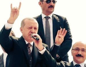 Het bondgenootschap in beeld: op een verkiezingsbijeenkomst in maart maakte Erdoğan het fascistische Grijze Wolven-gebaar. De man naast hem maakt tegelijk het gebaar van de fundamentalisten van de Egyptische Moslimbroederschap.