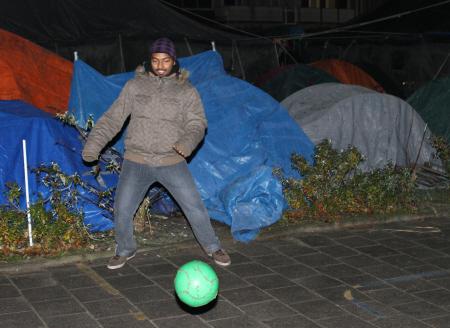 Aan de vooravond van de ontruiming van het Amsterdamse tentenkamp: vluchtelingen laten zich niet weerhouden van een partijtje voetbal. (foto: Jan Kees Helms)